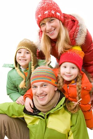 Happy family in winter clothes looking at camera and smiling photo