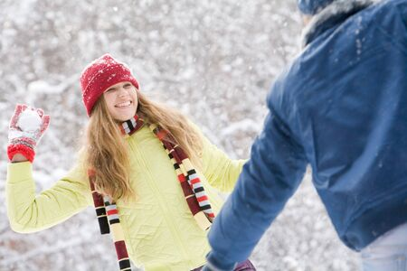 Image of attractive young woman flinging the snowball into her boyfriend photo