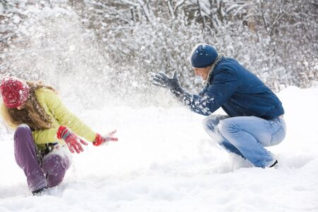 snowdrift: Portrait of happy couple sitting in snowdrift and playing snowballs in winter forest  Stock Photo
