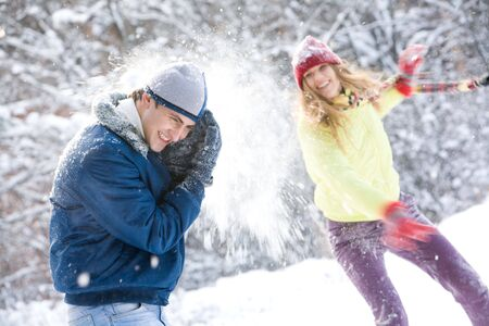 Image of young woman flinging the snowball into her boyfriend photo