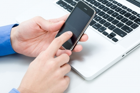 portable information device: Photo of male hand holding cellular phone and touching its sensor screen