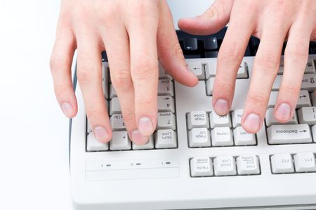 Above angle of male hands touching buttons of white computer keyboard photo