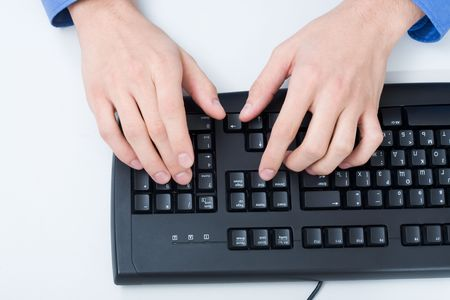 Close-up of male hand touching buttons of black computer keyboard photo