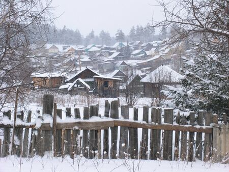 flurry: View of snow-covered wooden huts with pines at background