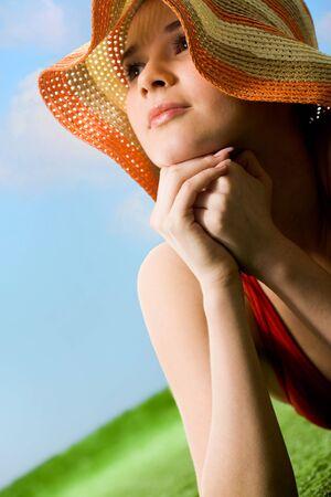 Portrait of happy woman in hat enjoying hot summer day photo