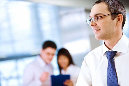 Image of handsome businessman in eyeglasses on background of his colleagues  photo