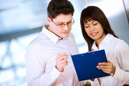 Photo of handsome boss looking at notes in secretary�s hand photo