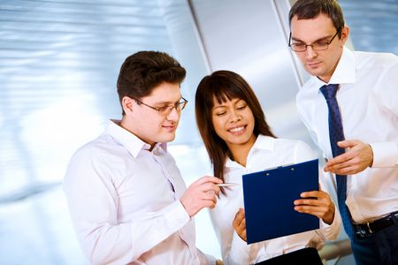 Photo of confident employees looking at notes in female hand photo