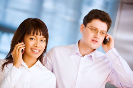 Image of confident woman and serious businessman speaking on the phone Stock Photo - 6637830