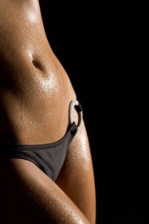navel: Image of luxurious woman torso in bikini on black background Stock Photo