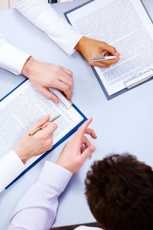 Photo of business people hands working with documents at briefing photo