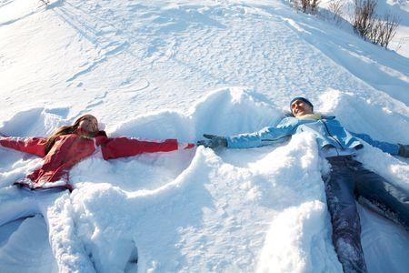 snowdrift: Photo of happy guy and joyful girl lying in snowdrift during winter vacation Stock Photo