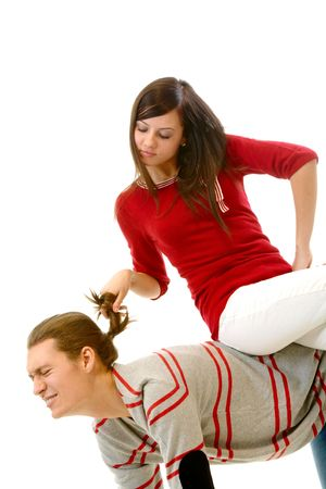 pulling hair: Portrait of attractive young girl pulling her boyfriend hair while sitting on his back