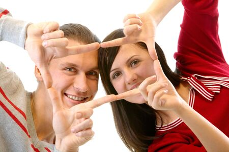 Portrait of attractive couple making frame from fingers and looking through it at camera photo