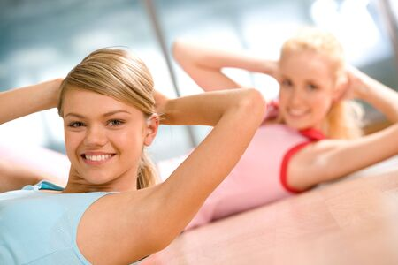Photo of cheerful girls doing exercise on the floor of sport gym photo