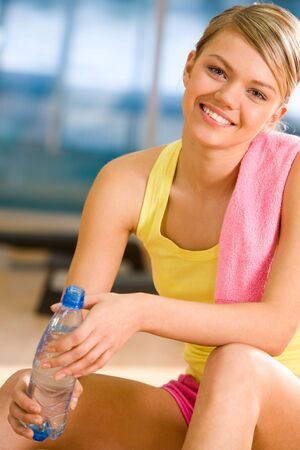 Portrait of happy woman wearing yellow tanktop looking at camera with smile in gym Stock Photo - 6637831