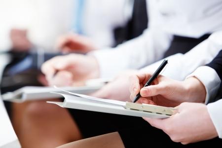Close-up de manos de personas de negocios con documentos sentado en la Conferencia