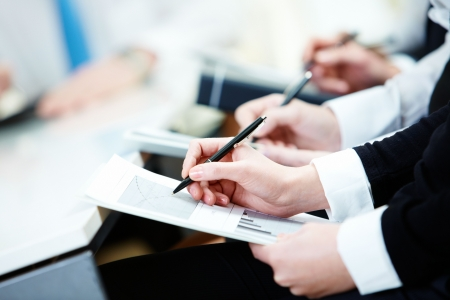 Close-up of business person hands with document writing at lecture  photo