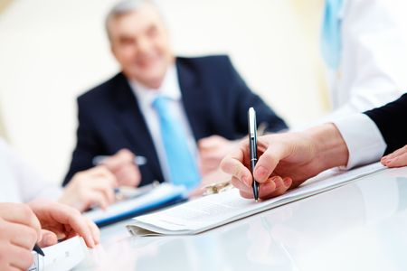Close-up of secretary hands over document with her boss on background Stock Photo - 6669668