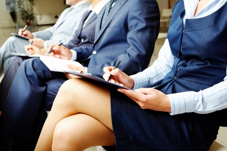 briefing: Photo of documents lying on business people�s legs at briefing  Stock Photo
