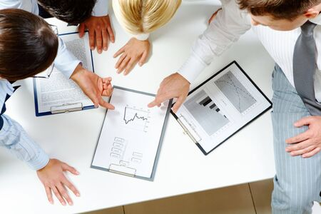 Above view of friendly workteam discussing business-plan Stock Photo - 6669614
