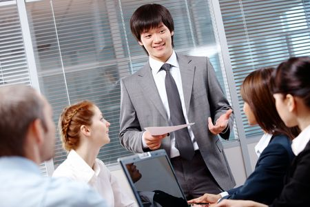 Photo of confident businessman making report to partners at conference photo