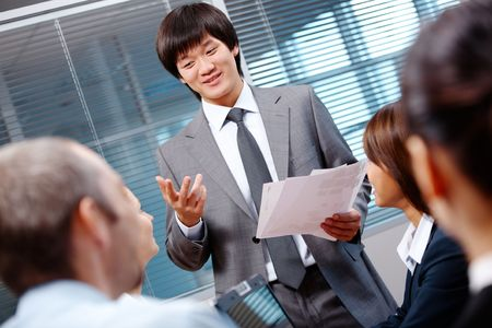 Photo of confident businessman making report to partners at seminar photo