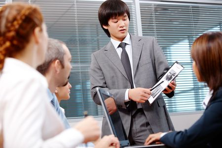 Photo of confident leader pointing at paper with diagrams during meeting photo