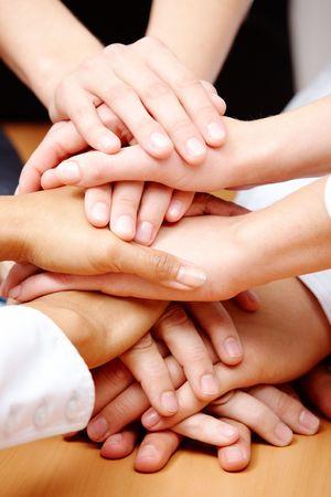 compa�erismo: Imagen de asociados de negocios de manos en la parte superior de cada uno a otro que simboliza el compa�erismo y la unidad