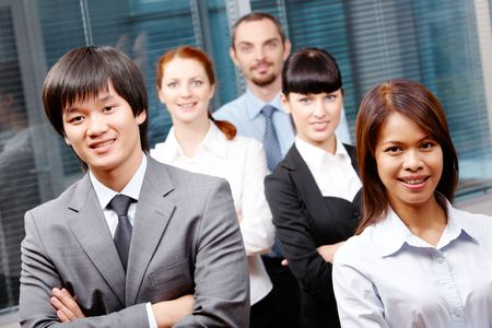 Photo of successful business partners looking at camera with co-workers behind them photo