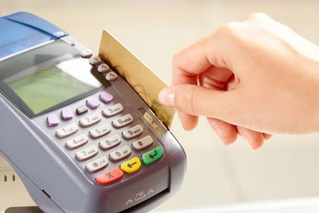 Close-up of payment machine buttons with human hand holding plastic card near by photo