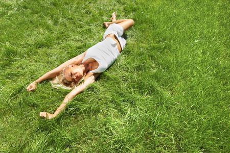 Above view of pretty blonde lying on green grass and stretching up photo