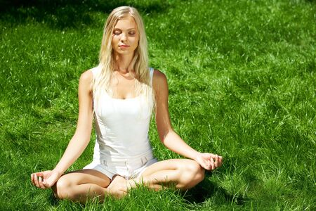 Image of meditating girl seated in pose of lotus on green grass  photo