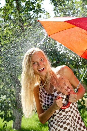 Portrait of happy girl with red umbrella in hands laughing at camera in park photo