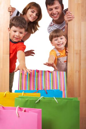Image of cheerful family members looking at colorful shopping bags with happy expression photo