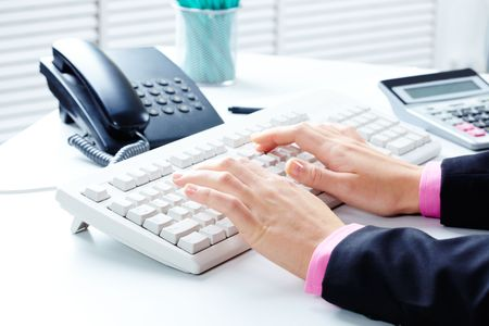 Close-up of female�s hands touching keys of laptop in office photo