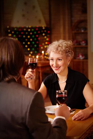 Image of happy female toasting in restaurant while looking at her sweetheart photo