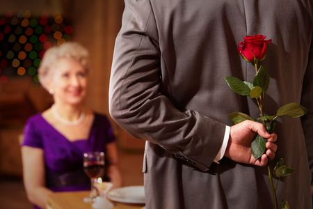 intrigued: Rear view of man holding red rose in hand on background of intrigued female Stock Photo