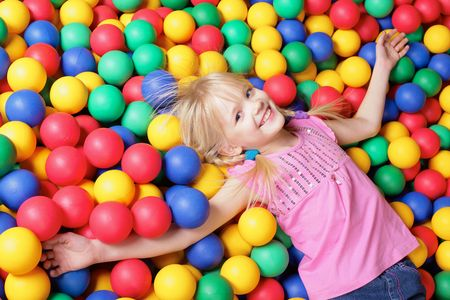 Happy girl lying on colorful balls and looking at camera Stock Photo - 6670127