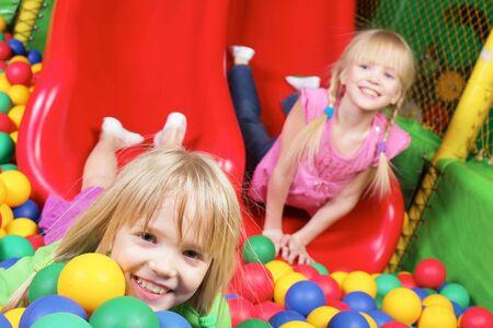 soeur jumelle: Heureuse fille regardant cam�ra avec sa soeur jumelle sur fond  Banque d'images