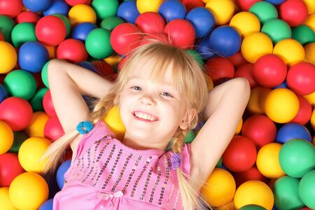Happy girl lying on colorful balls and smiling  Stock Photo - 6669858