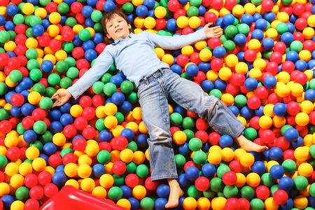 Happy lad seated on colorful balls and looking at camera with smile Stock Photo - 6669852
