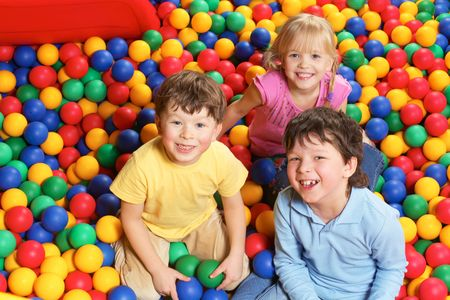 Happy lads and girl laughing while having fun in colorful balls Stock Photo - 6670130