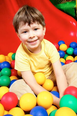 Happy lad looking at camera while sitting in balls Stock Photo - 6669856