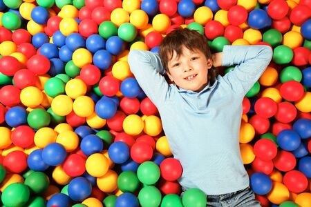 arms above head: Happy lad lying on colorful balls and looking at camera with smile