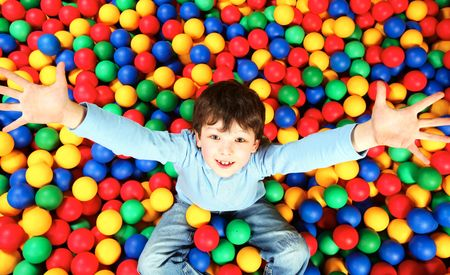 Happy lad seated on colorful balls and stretching arms to camera Stock Photo - 6670133