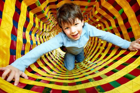 lad: Happy lad looking at camera while having fun inside toy tunnel