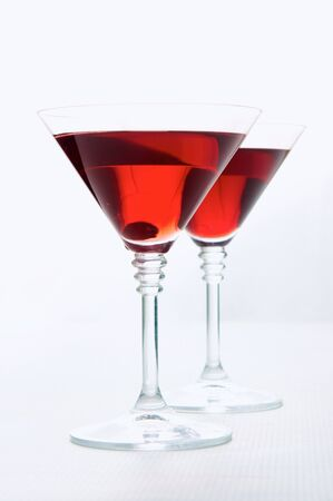 Two martini glasses with red wine over white background photo