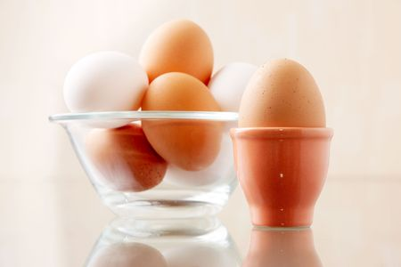 Image of fresh egg in ceramic form on background of several other ones in bowl photo