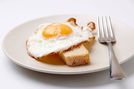 Image of fried egg on plate served with piece of wheat bread Stock Photo - 6669842